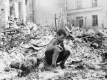 A-young-Polish-boy-returns-to-what-was-his-home-and-squats-among-the-ruins-during-a-pause-in-the-German-air-raids-on-Warsaw-Poland-in-September-of-1939.-German-attacks-lasted-until-Warsaw-surrendered-on-September-28.-